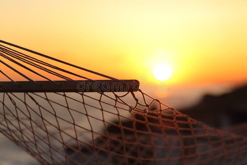 Ciérrese para arriba de una hamaca en la playa en la puesta del sol imagen de archivo libre de regalías