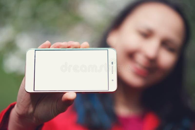Ciérrese para arriba de una hembra que muestra una pantalla horizontal en blanco del teléfono en la calle foto de archivo
