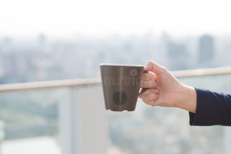 Ciérrese para arriba de una mano de la mujer que sostiene una taza de café al lado de una ventana con un exterior verde del fondo foto de archivo libre de regalías