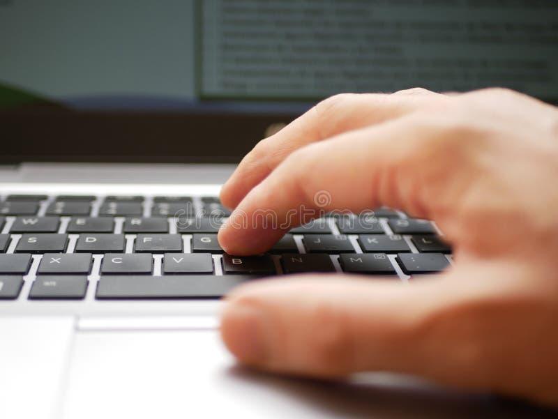 Ciérrese para arriba de una mano de un hombre que trabaja sobre un ordenador portátil y que usa el cojín de la pista imagen de archivo