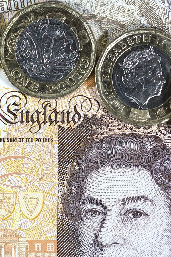 Ciérrese para arriba de una moneda de una libra con un fondo de la nota de diez libras - moneda británica imagen de archivo