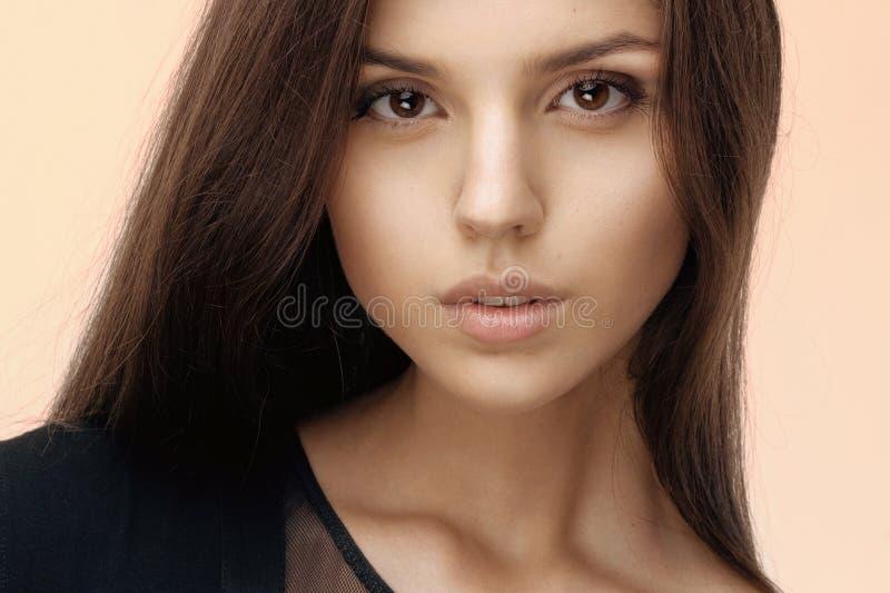 Ciérrese para arriba de una muchacha morena con atractivo y natural componga, pelo largo, mirando la cámara, vestida en negro fotografía de archivo