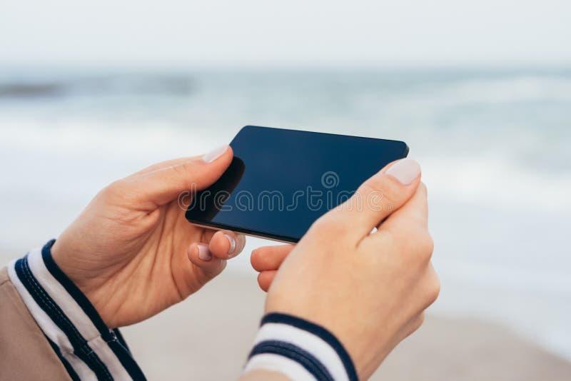 Ciérrese para arriba de una mujer en la capa beige en la playa que mira la pantalla elegante del teléfono fotos de archivo libres de regalías