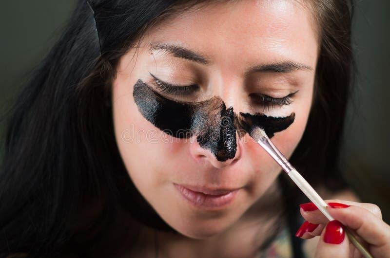 Ciérrese para arriba de una mujer joven de la belleza aplying en su cara una máscara negra para limpiar la piel imagenes de archivo