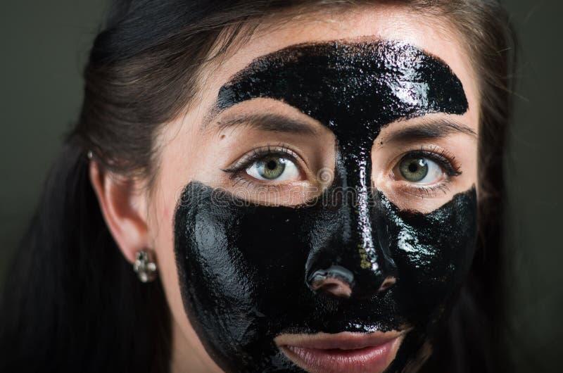 Ciérrese para arriba de una mujer joven de la belleza que usa una máscara negra para limpiar la piel imágenes de archivo libres de regalías