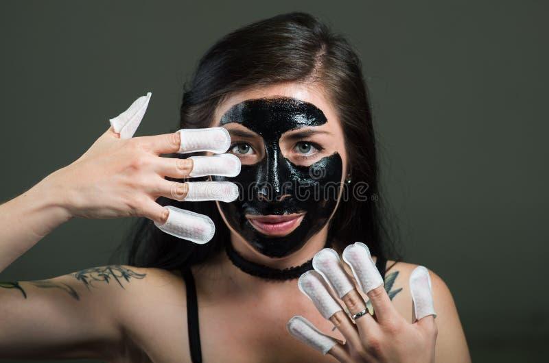 Ciérrese para arriba de una mujer joven de la belleza que usa una mascarilla negra y llevando el protector de los clavos en sus c imagen de archivo