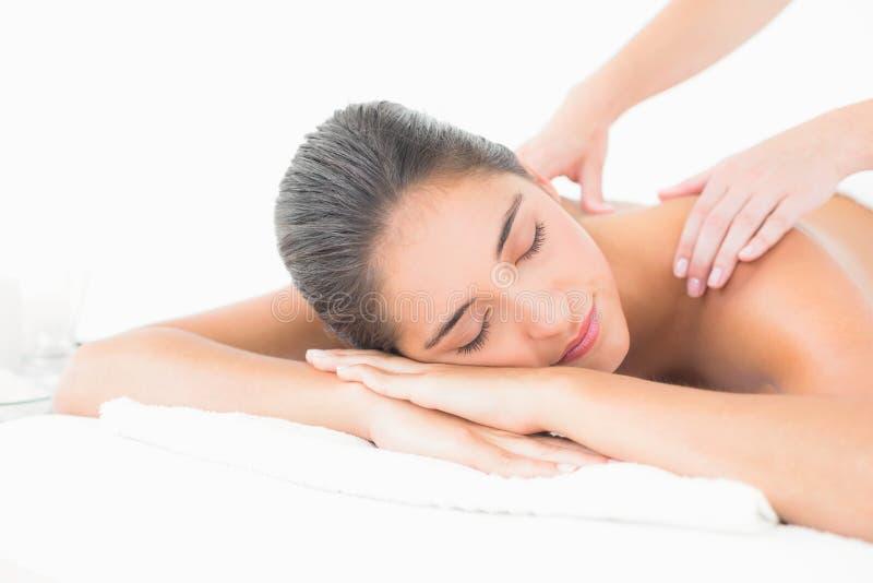 Ciérrese para arriba de una mujer joven hermosa en la tabla del masaje imagen de archivo