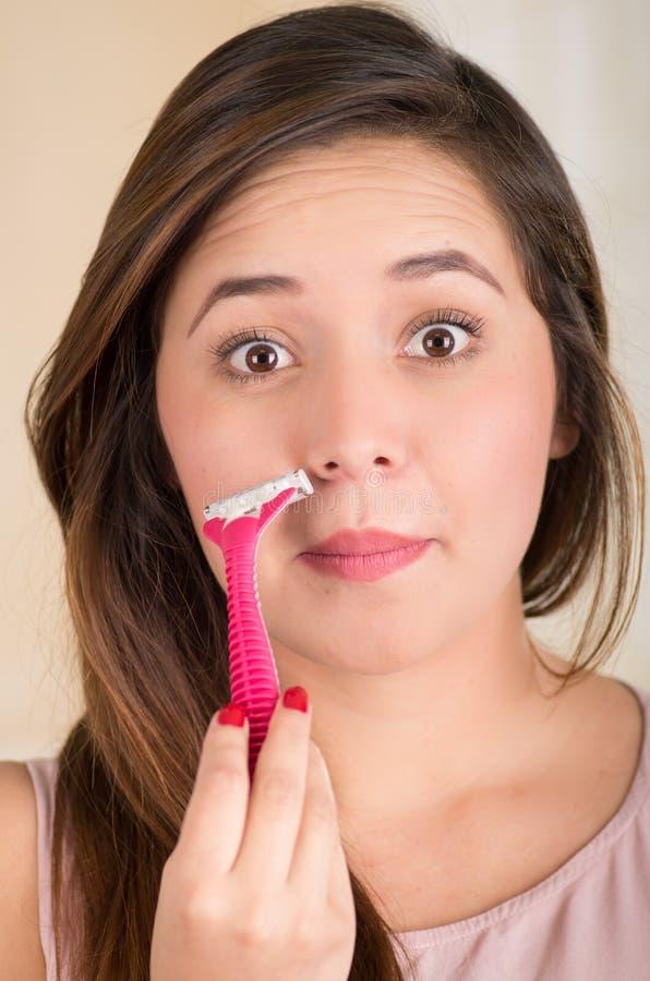 Ciérrese para arriba de una mujer joven hermosa que usa una máquina de afeitar que finge afeitar su bigote, en un fondo blanco imagen de archivo libre de regalías