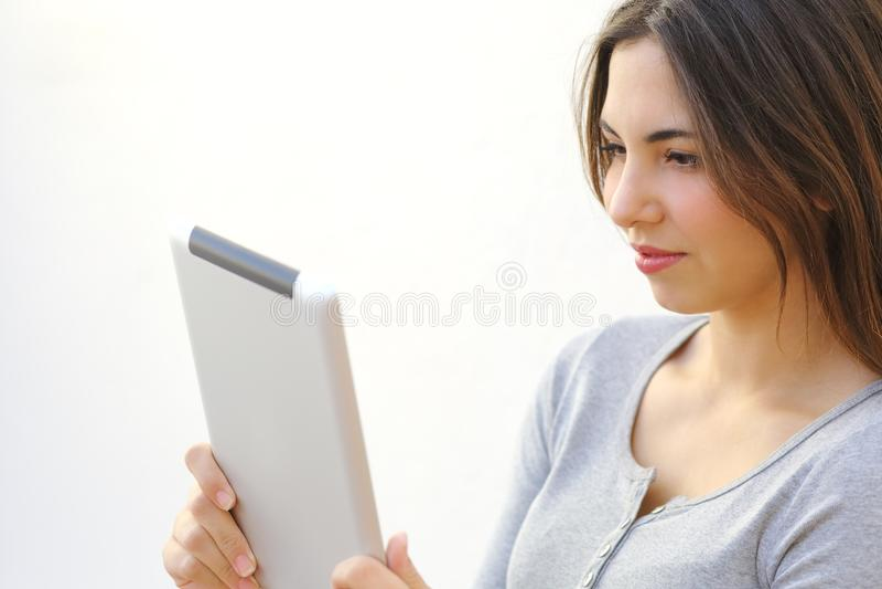 Ciérrese para arriba de una mujer joven que lee a un lector de la tableta al aire libre imagen de archivo