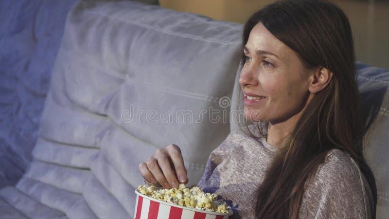 Ciérrese para arriba de una mujer madura que come las palomitas que sonríen en el cine imagenes de archivo