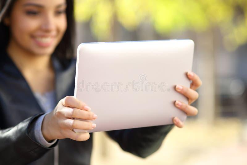Ciérrese para arriba de una mujer que sostiene y que mira una tableta digital imagen de archivo