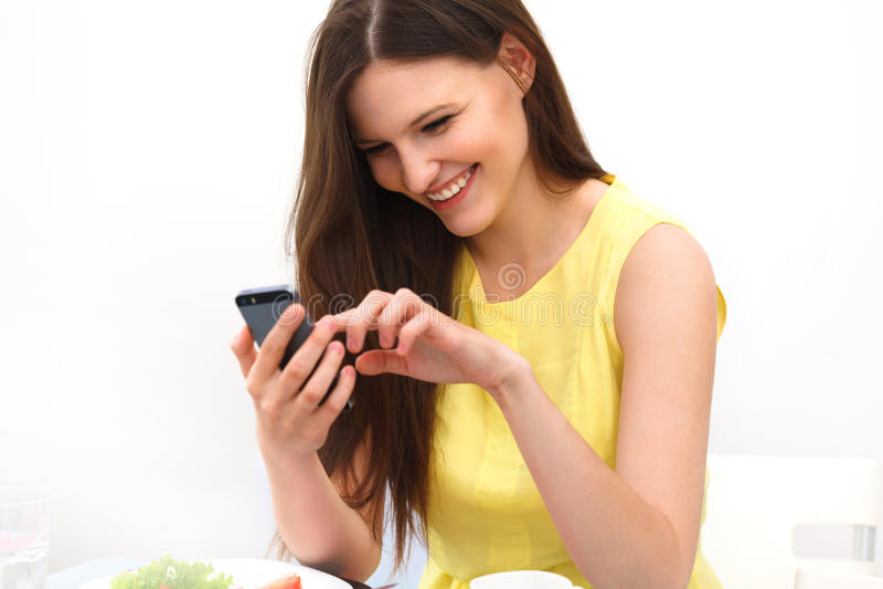 Ciérrese para arriba de una mujer que usa el teléfono elegante móvil fotografía de archivo