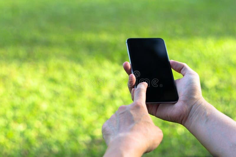 Ciérrese para arriba de una mujer que usa el teléfono elegante móvil con la pantalla táctil d imagen de archivo libre de regalías