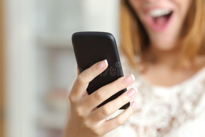 Ciérrese para arriba de una mujer sorprendida que usa un teléfono elegante en casa foto de archivo