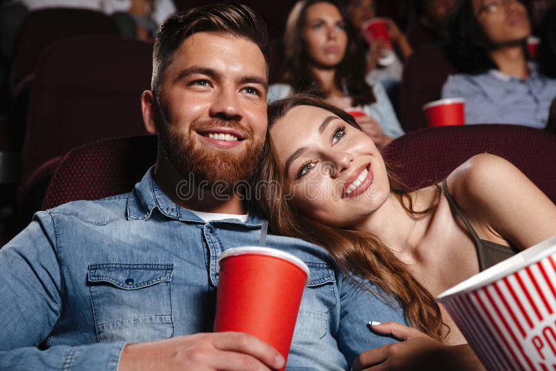 Ciérrese para arriba de una película de observación sonriente de los pares jovenes imágenes de archivo libres de regalías