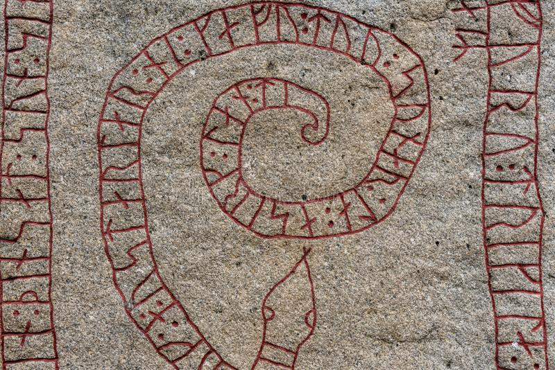 Ciérrese para arriba de una piedra vieja de la runa con las runas rojas en la forma de un s imagen de archivo libre de regalías