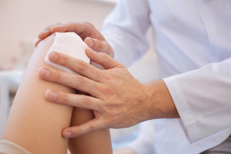 Ciérrese para arriba de una preparación médica que es presionada a la herida imagen de archivo