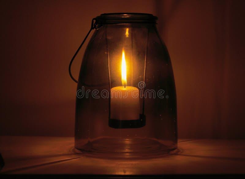 Ciérrese para arriba de una vela ardiente puesta dentro de un beneficiario de cristal antiguo de n foto de archivo