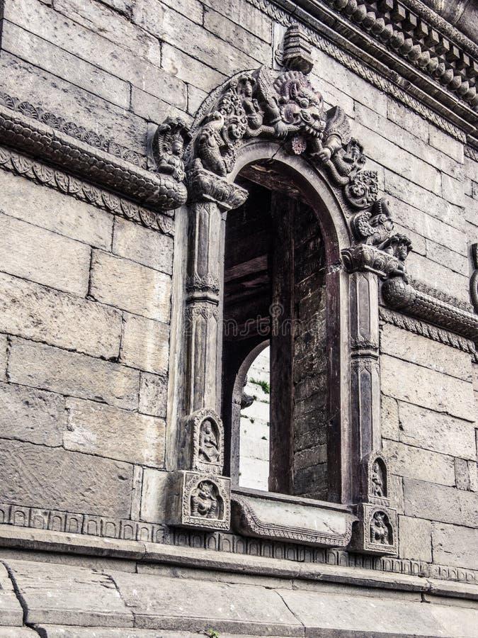 Ciérrese para arriba de una ventana en el edificio sagrado de piedra viejo Pashupatina foto de archivo