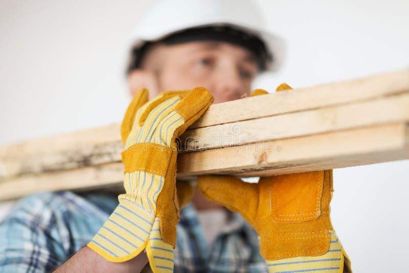 Ciérrese para arriba de varón en los guantes que llevan a los tableros de madera fotos de archivo