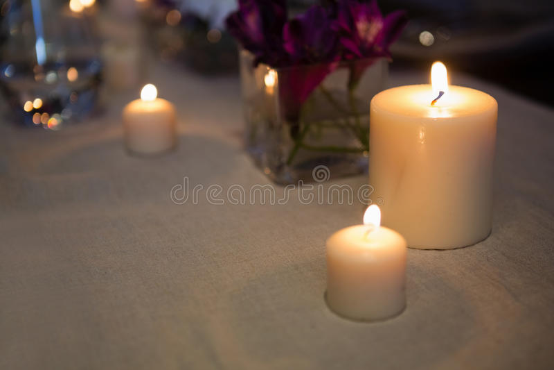 Ciérrese para arriba de velas encendidas en la tabla fotos de archivo libres de regalías