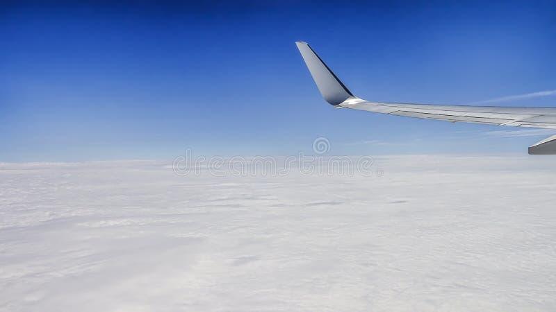 Ciérrese para arriba de ventana con el ala del aeroplano Cloudscape hermoso con el cielo azul claro fotos de archivo libres de regalías