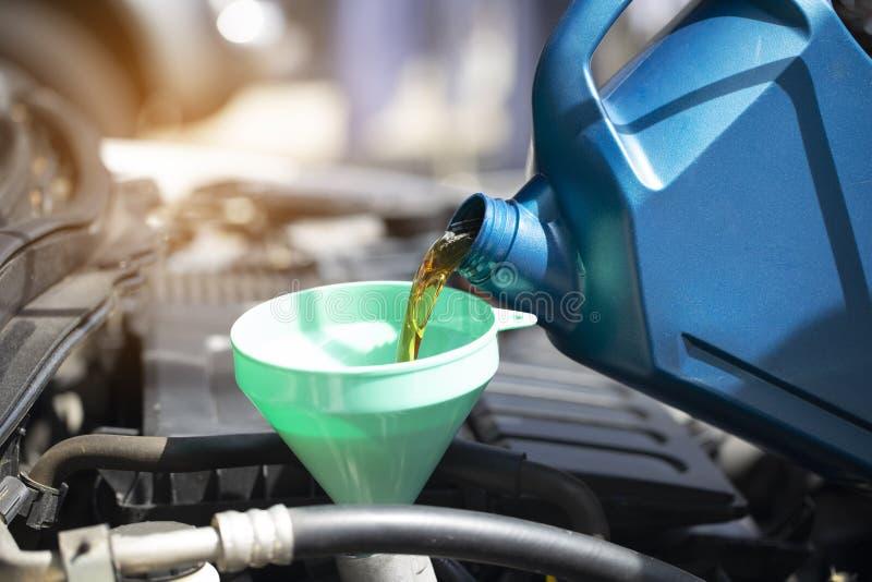 Ciérrese para arriba de verter el aceite fresco al motor de coche en servi de la reparación auto fotos de archivo libres de regalías