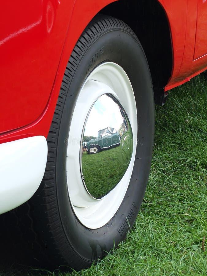 Ciérrese para arriba de vieja vw combi van wheel con un mini del verde del vintage reflejada en el tapacubos del cromo en el vint imagen de archivo