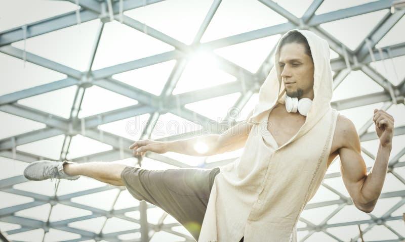Ciérrese para arriba de yoga practicante del hombre atlético en parque moderno debajo de la bóveda de cristal imagen de archivo