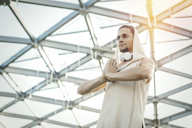 Ciérrese para arriba de yoga practicante del hombre atlético en parque moderno debajo de la bóveda de cristal imagenes de archivo
