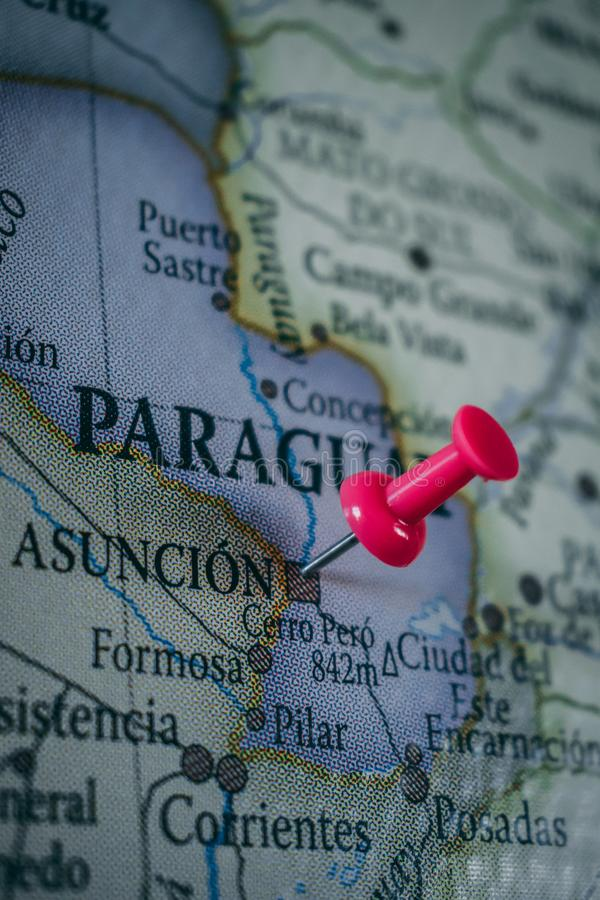 Ciérrese para arriba del ³ n, perno de Asuncià de Paraguay señaló en el mapa del mundo con un pasador rosado fotografía de archivo