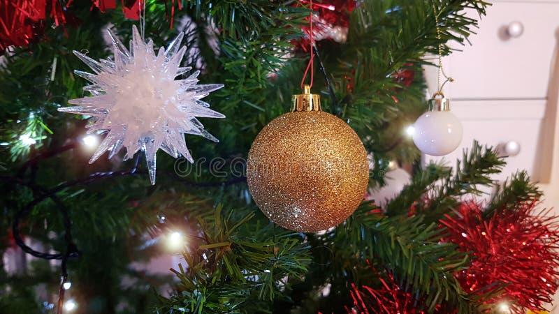 Ciérrese para arriba del árbol de navidad artificial con el ornamento hermoso de la Navidad con la bola redonda de oro y el copo  imágenes de archivo libres de regalías