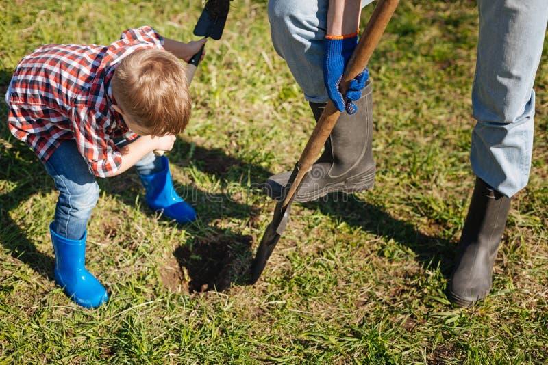 Ciérrese para arriba del abuelo y del niño pequeño que sacan con pala en jardín imagen de archivo libre de regalías