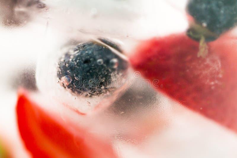 Ciérrese para arriba del agua de la fruta con los cubos de hielo sobre el vidrio fotos de archivo