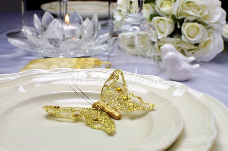 Ciérrese para arriba del ala butterful del oro en las placas de la tabla de la boda imagen de archivo