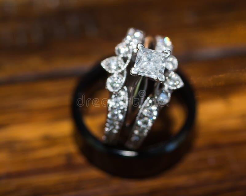 Ciérrese para arriba del anillo de bodas de las novias que se sienta en anillo de bodas de los novios imagenes de archivo