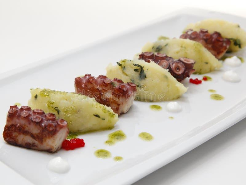 Ciérrese para arriba del aperitivo asado a la parrilla del pulpo con las pequeñas patatas fotografía de archivo