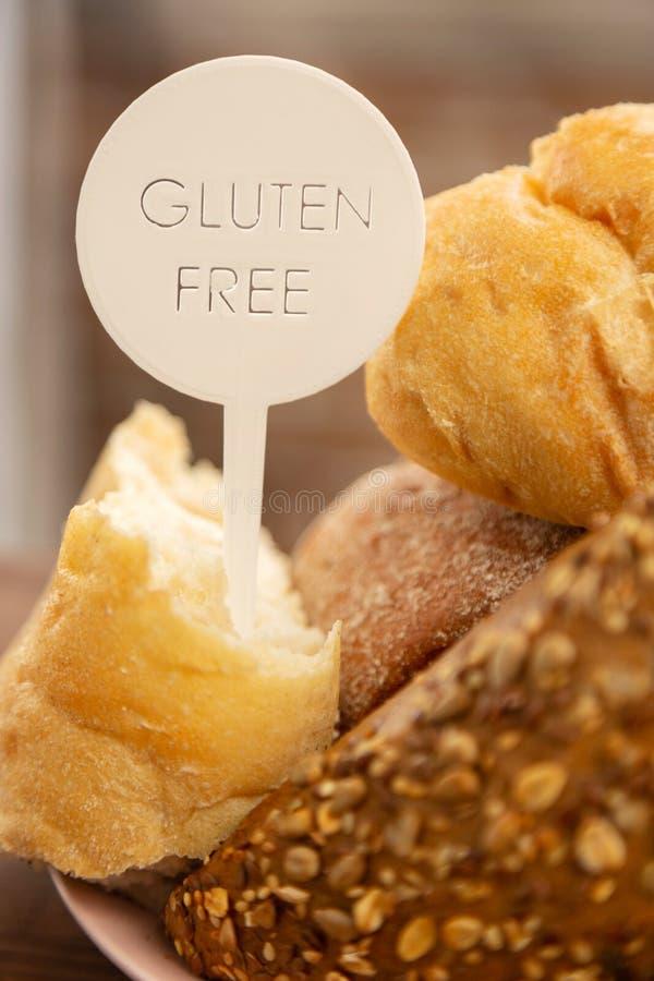 Ciérrese para arriba del baguette y de bollos sin el gluten en la placa foto de archivo libre de regalías