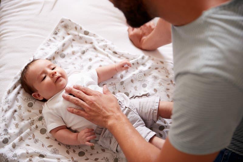 Ciérrese para arriba del bebé de amor de Lying With Newborn del padre en cama en casa en el apartamento del desván imagen de archivo