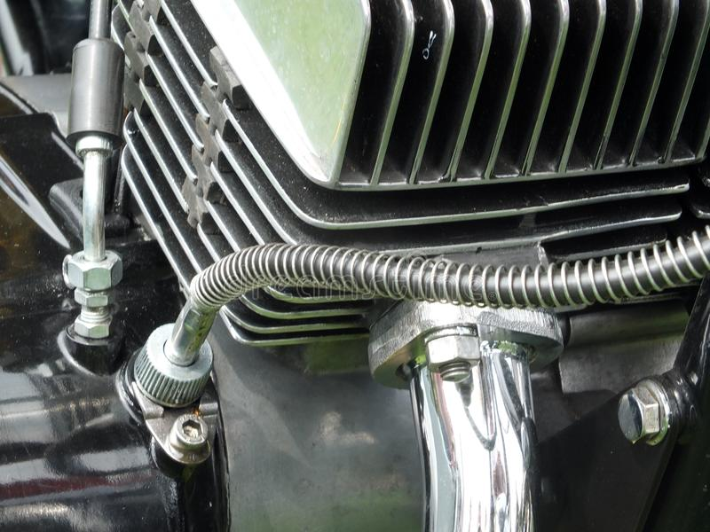 Ciérrese para arriba del bloque de motor de una motocicleta negra del vintage con los tubos brillantes y del cromo de culata del  foto de archivo