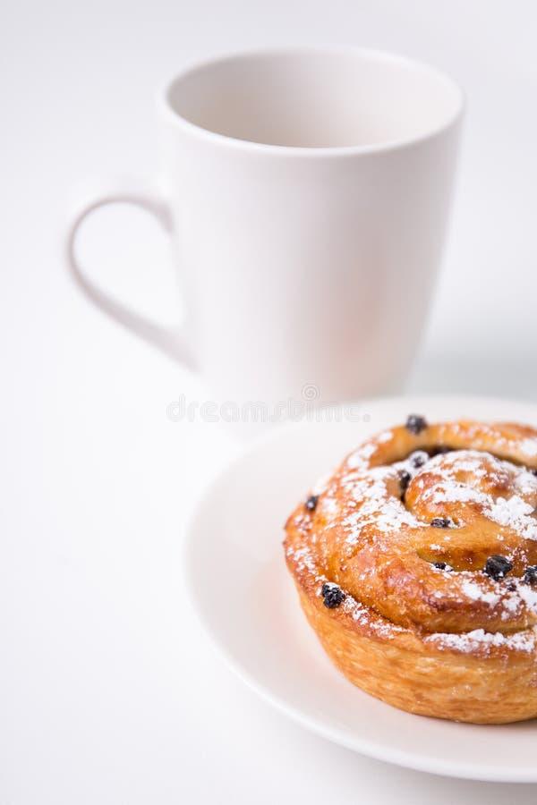 Ciérrese para arriba del bollo dulce con las pasas y la taza de café o de té encima imagen de archivo libre de regalías