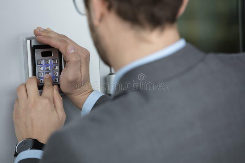 Ciérrese para arriba del botón del presionado a mano del hombre de negocios en el sistema de seguridad imágenes de archivo libres de regalías