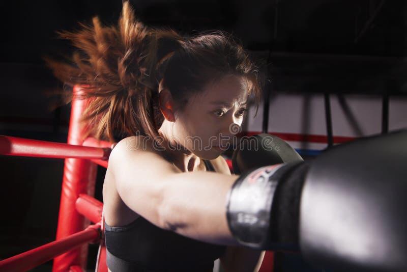 Ciérrese para arriba del boxeador de sexo femenino que lanza un sacador, pelo en el movimiento imágenes de archivo libres de regalías