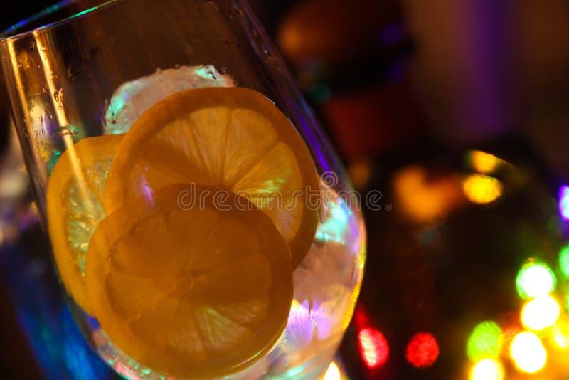 Ciérrese para arriba del cóctel con las rebanadas de cubos del limón y de hielo imagen de archivo libre de regalías
