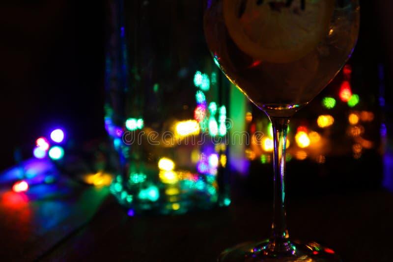Ciérrese para arriba del cóctel con las rebanadas de limón y los cubos y las botellas de hielo se centran en glas provienen fotos de archivo libres de regalías