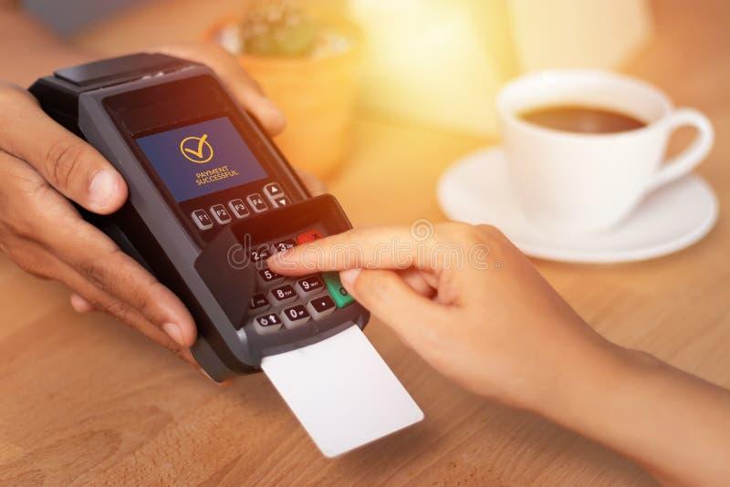 Ciérrese para arriba del código del perno de la tarjeta de crédito de la mano que entra para la contraseña de la seguridad en máq fotos de archivo libres de regalías