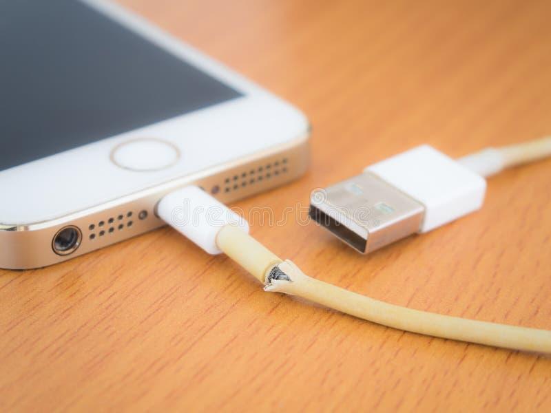 Ciérrese para arriba del cable quebrado del cargador del iPhone foto de archivo libre de regalías