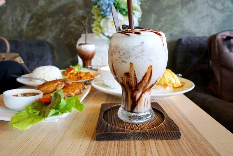 Ciérrese para arriba del café del frappe del chocolate con crema azotada en la tabla de madera foto de archivo