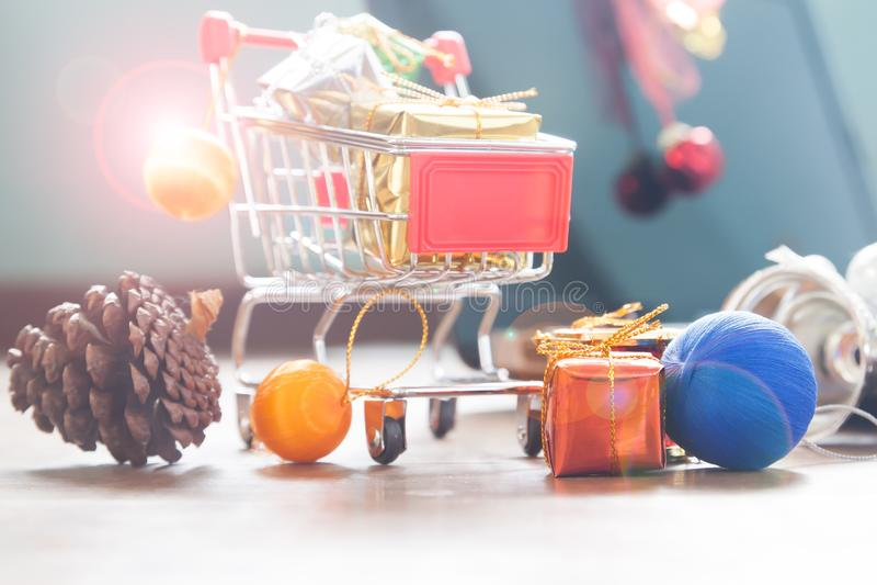 Ciérrese para arriba del carro de la compra con las cajas de regalo y las decoraciones de la Navidad imágenes de archivo libres de regalías