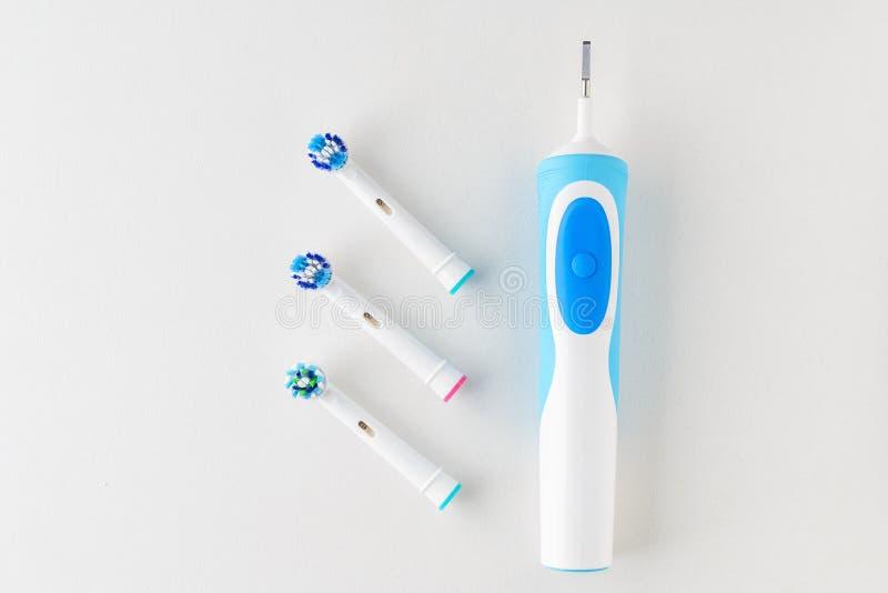 Ciérrese para arriba del cepillo de dientes eléctrico y ahorre las cabezas del cepillo en el fondo blanco imagenes de archivo
